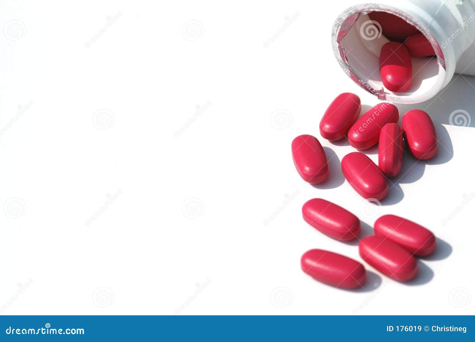 Píldoras rojas en el fondo blanco