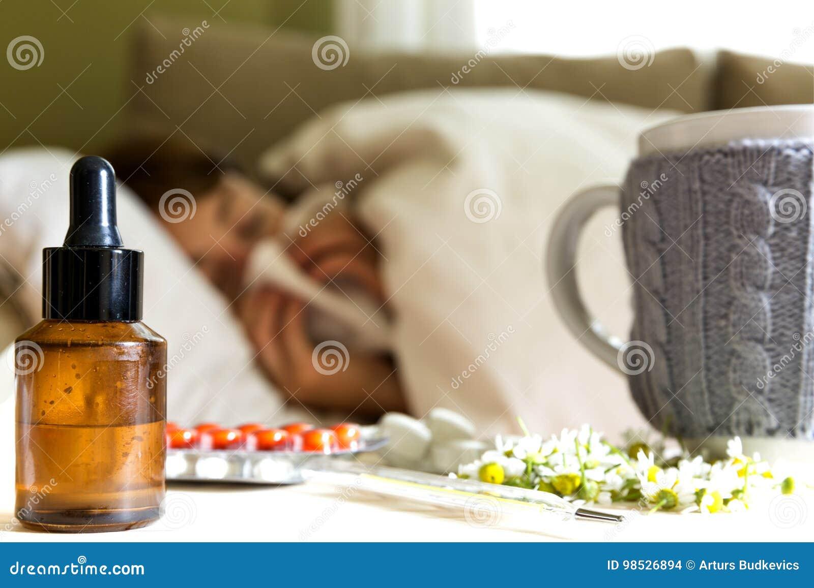 Píldoras, té de manzanilla y extracto homeopático en la tabla Mujer joven que miente en una cama cubierta con la manta que sopla