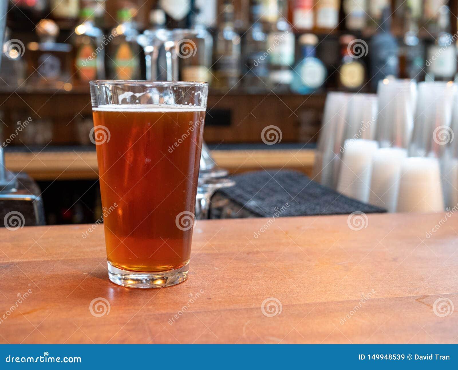 Pół kwartego szkło piwny obsiadanie na barze odpierającym w dnia czasie