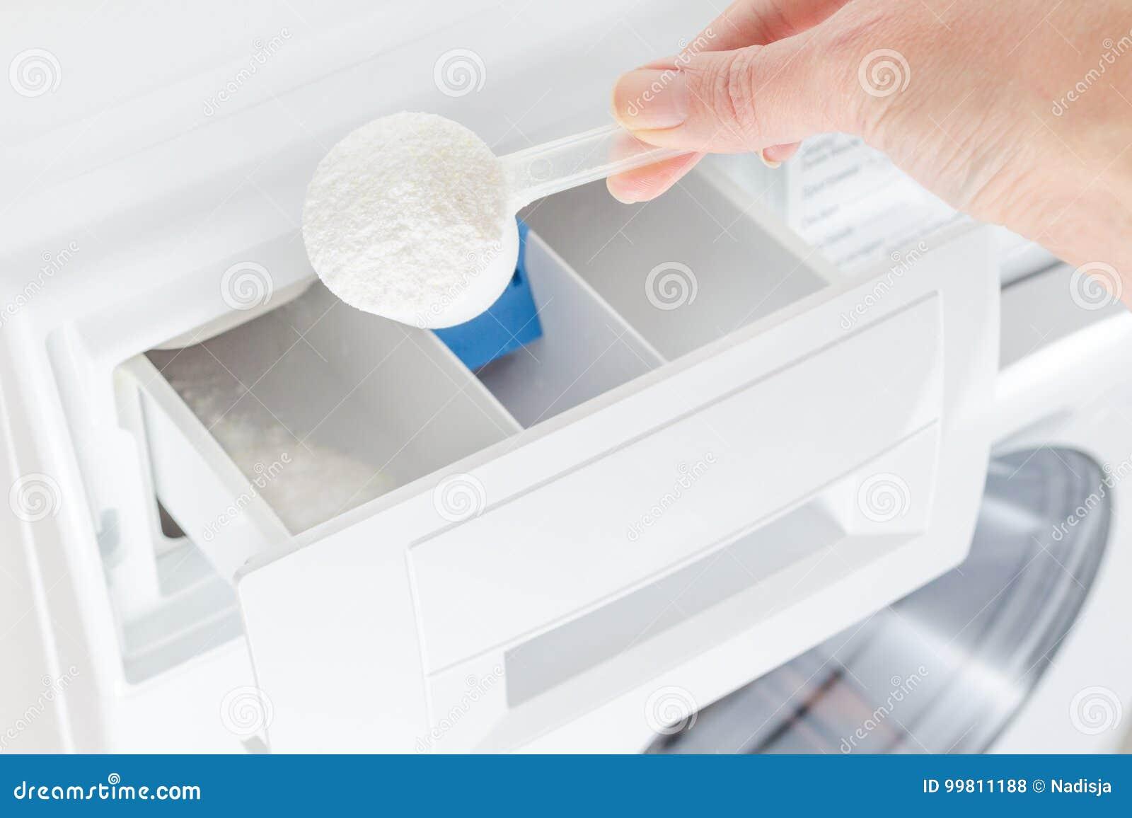 Pó de lavagem, detergente em um copo e mão da mulher, máquina de lavar, foco seletivo