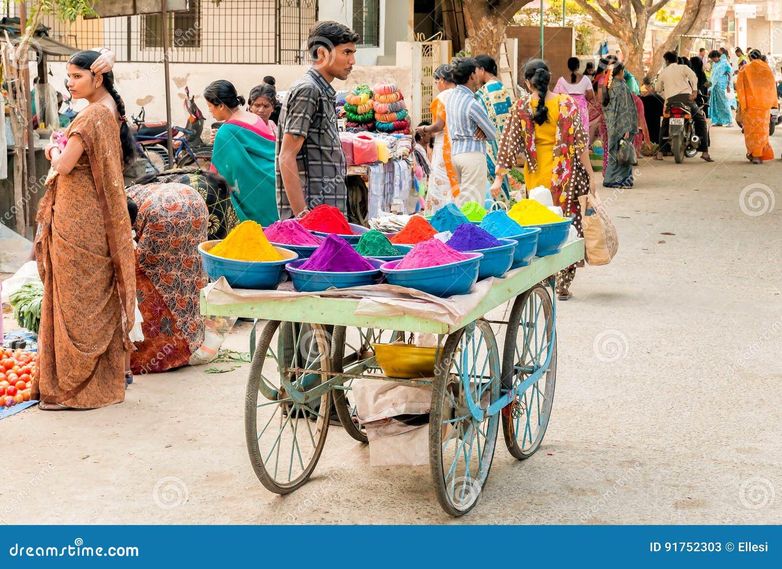 Pós coloridos do tika da venda do vendedor ambulante no mercado de rua de Puttaparthi, Índia