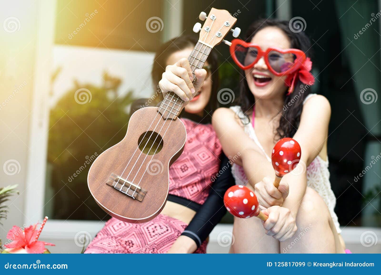 Pölpartiet, lyckliga kvinnor tycker om att spela musikinstrumentet, genom simbassängen, flickvänner i bikinileende och att skratt