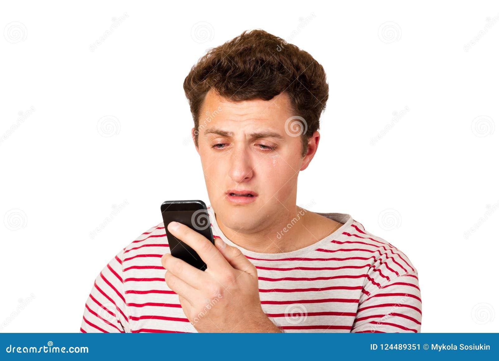 Płaczu mężczyzna czyta wiadomość tekstową na jego telefonie Sms z złą wiadomością emocjonalny mężczyzna odizolowywający na białym