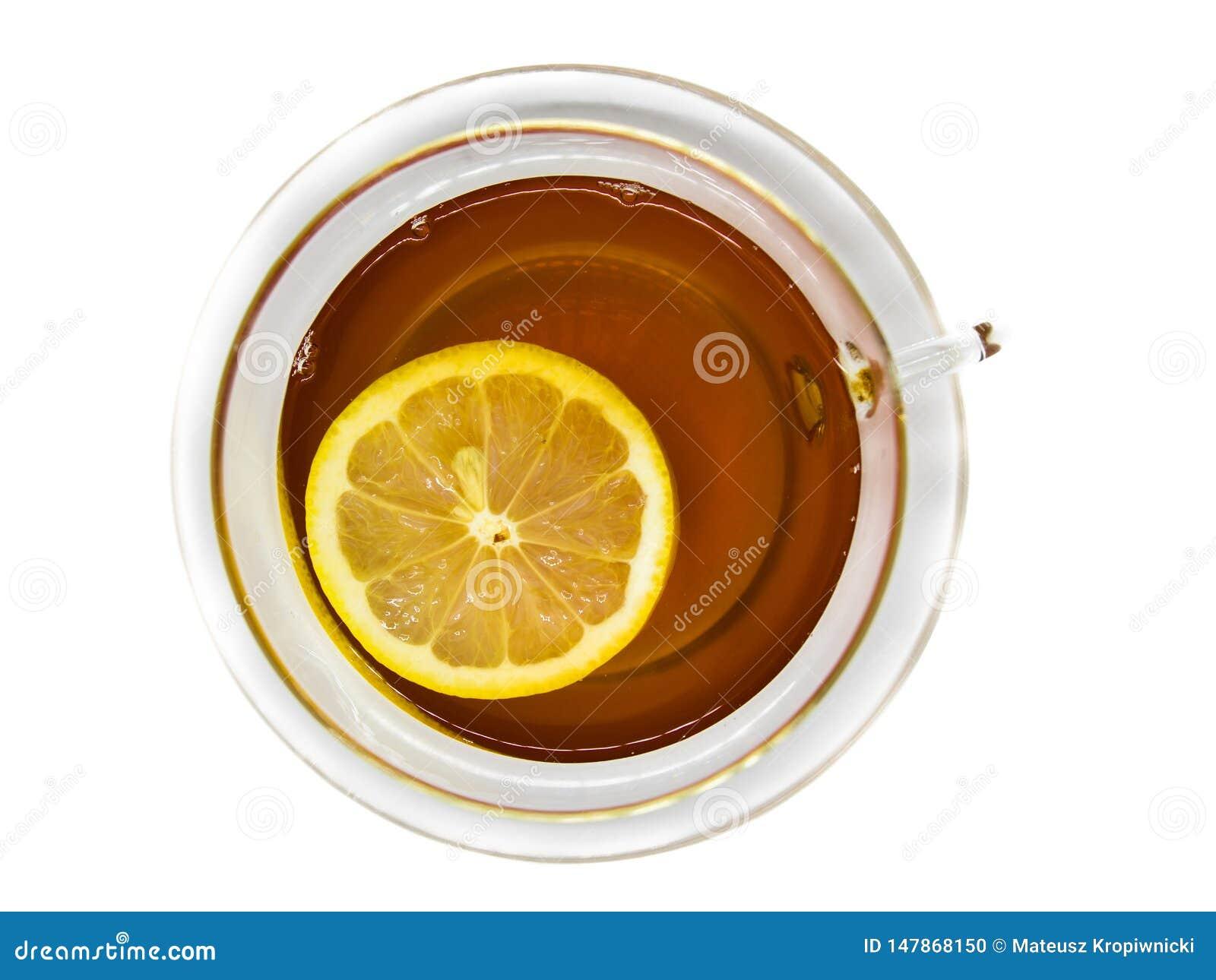 Płaski widok herbata w przejrzystej, szklanej filiżance z spławowym cytryna plasterkiem na białym tle,