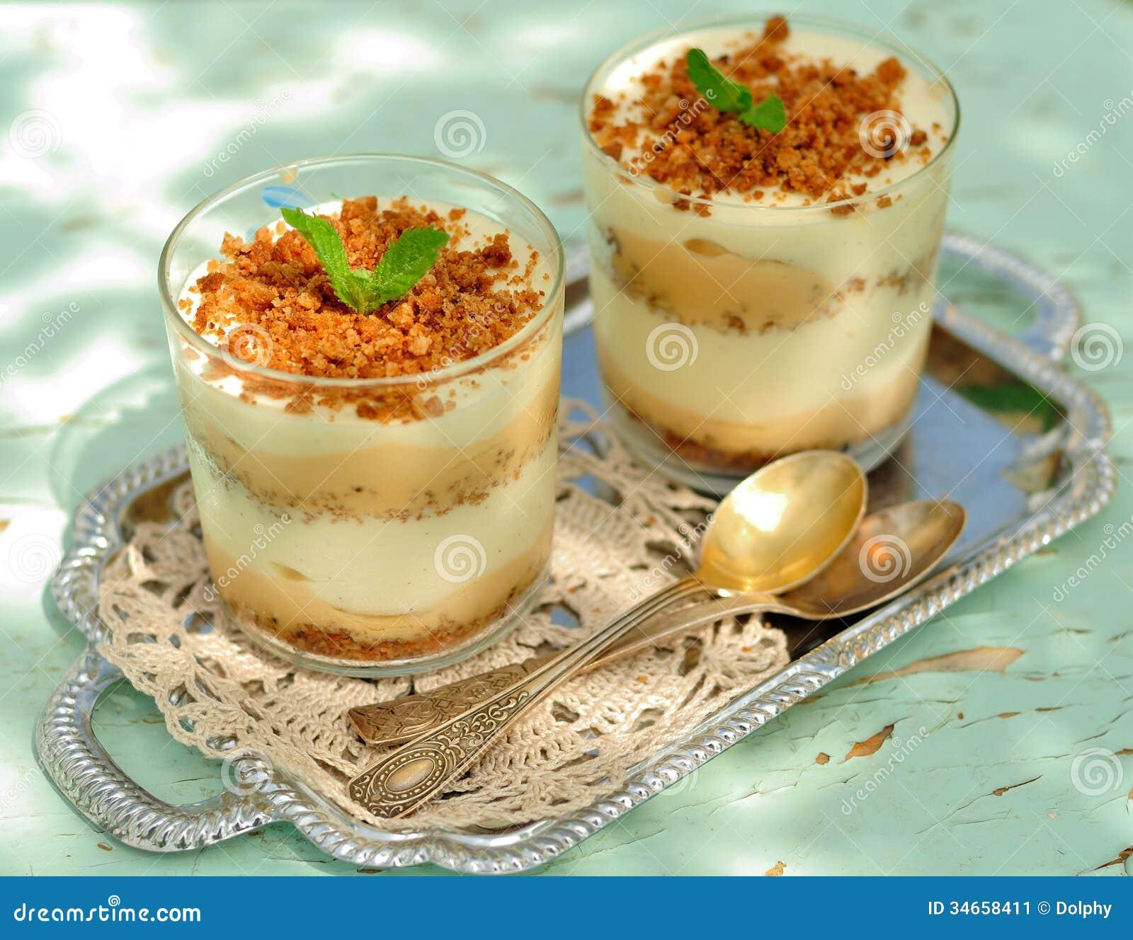 Płatowaty deser w szkłach, pokruszonym ciastku, karmelu kumberlandzie, waniliowym custard i bananach,