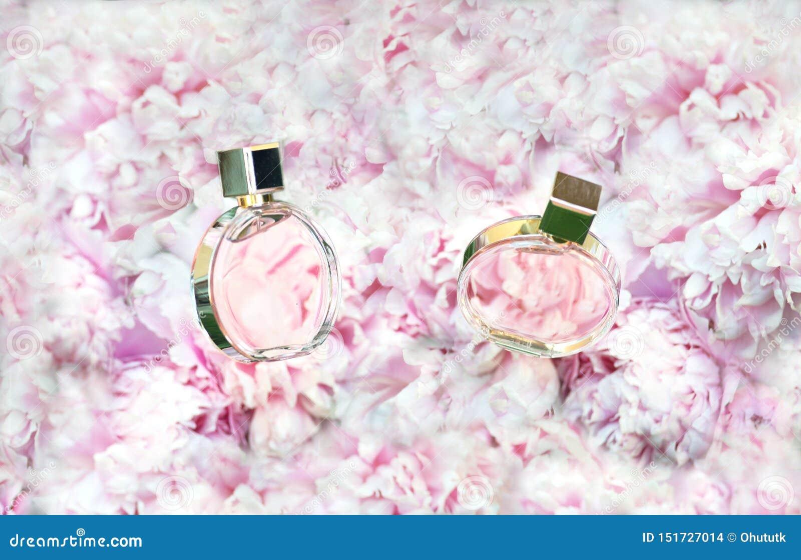 Płodozmienne pachnidło butelki na menchiach kwitną peoni tło z kopii przestrzenią Mydlarnia, kosmetyki, żeńscy akcesoria