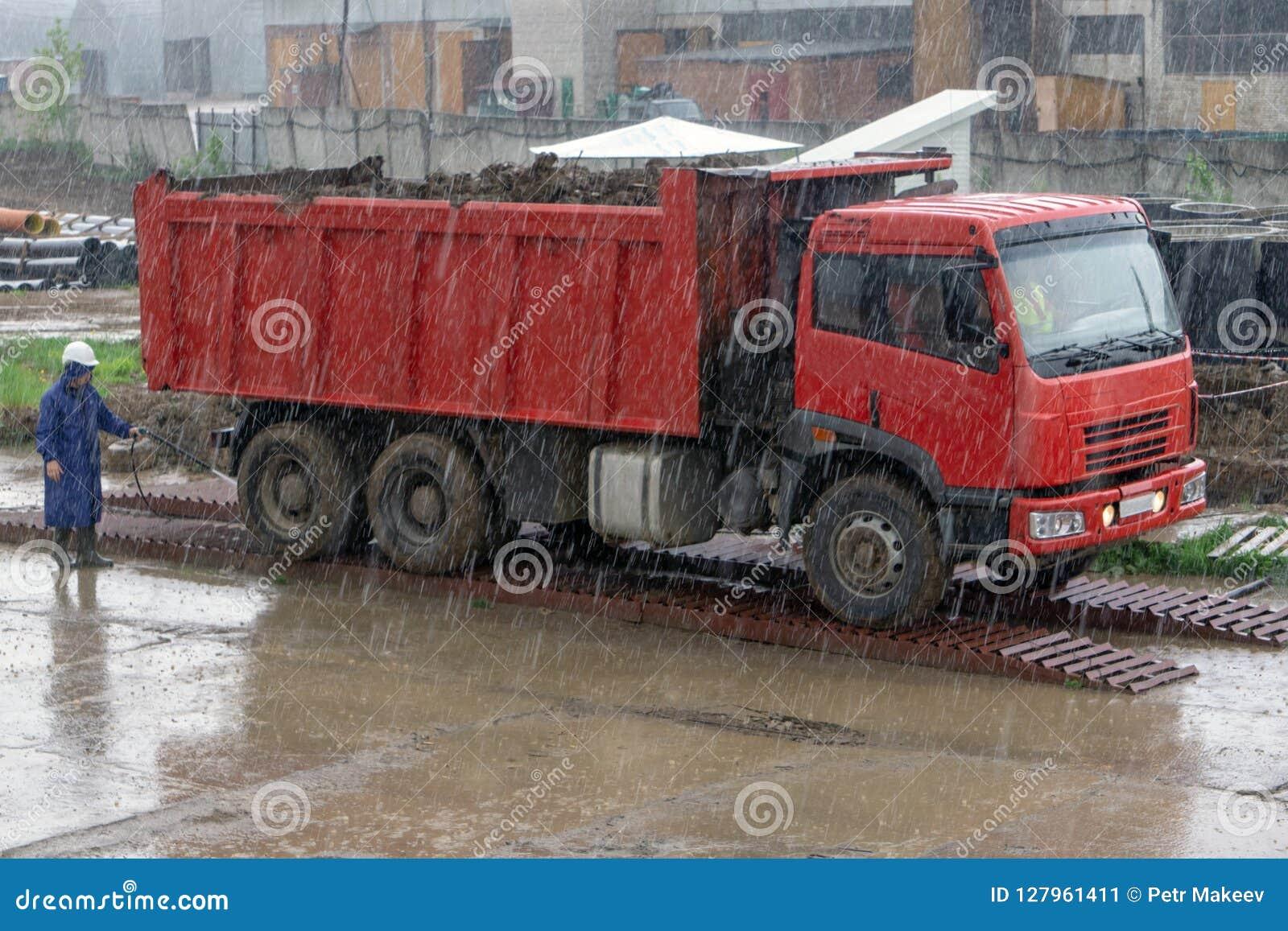 Płuczka myje samochód pod deszczem