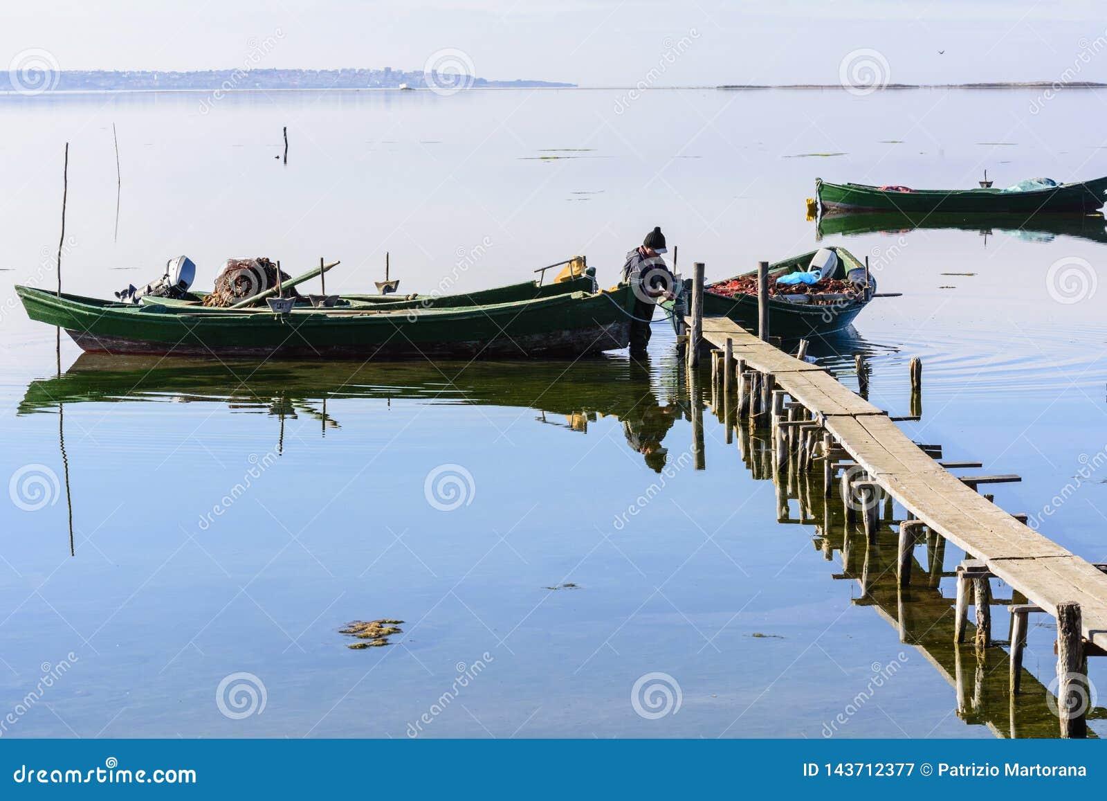P?cheurs avec leurs bateaux antiques, chute ? l aube Sud de la Sardaigne occidentaux