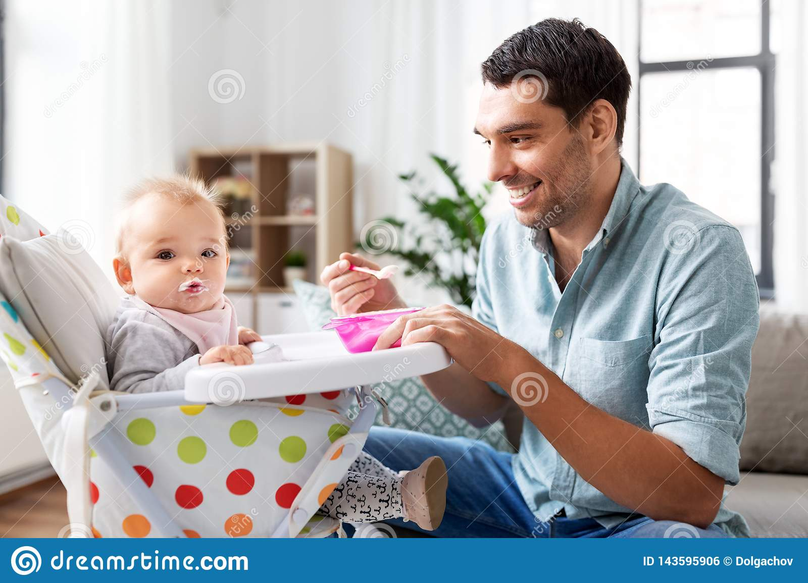 P?re alimentant le b?b? heureux dans le highchair ? la maison