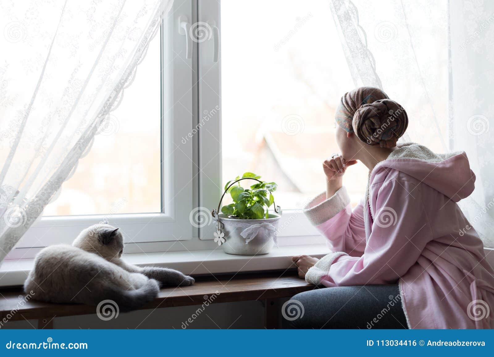 Pañuelo que lleva y albornoz del enfermo de cáncer joven de la hembra adulta que se sientan en la cocina con su gato del animal d