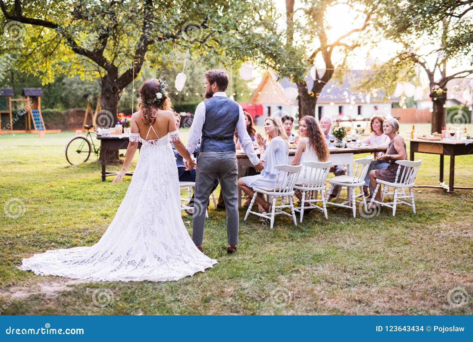 Państwa młodzi mienia ręki przy weselem outside w podwórku