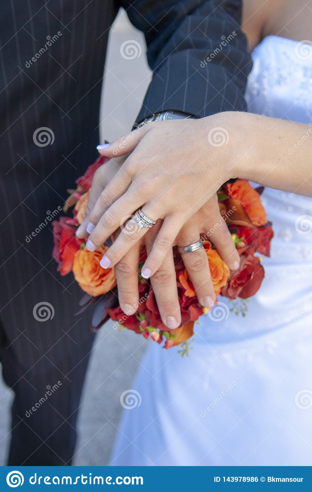 Państwa młodzi ręki, pierścionki i bukiet,