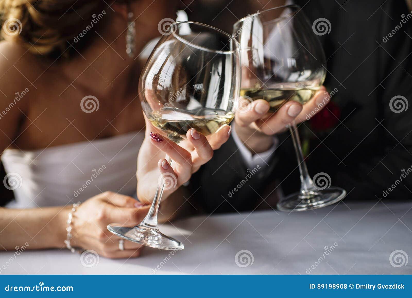 Państwo młodzi z szkłami wino w rękach