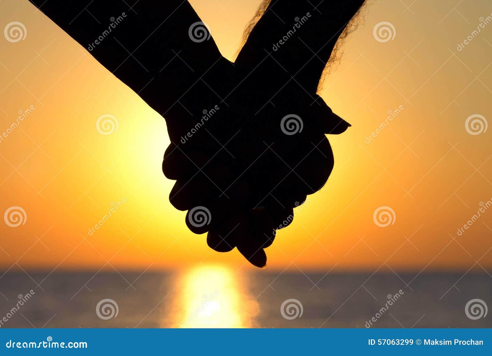 Paar bij de handen van de zonsondergangholding