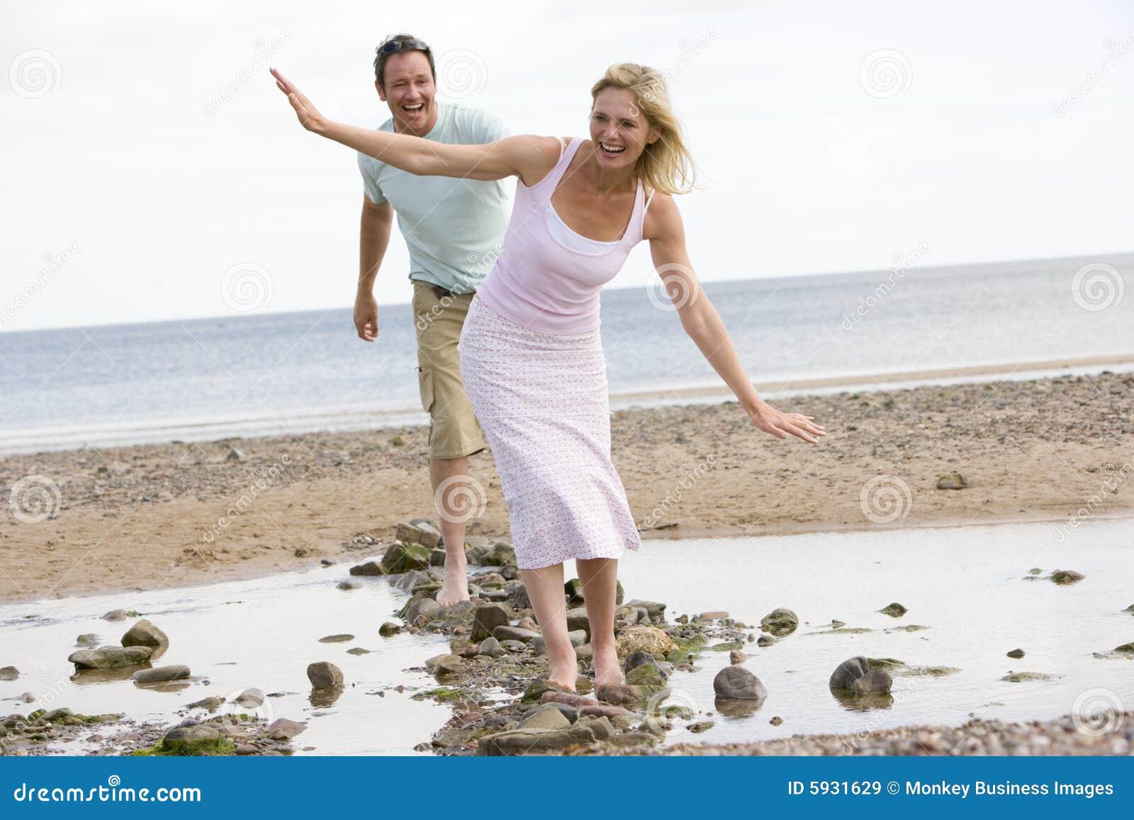 Paar bij het strand dat bij stenen en het glimlachen loopt