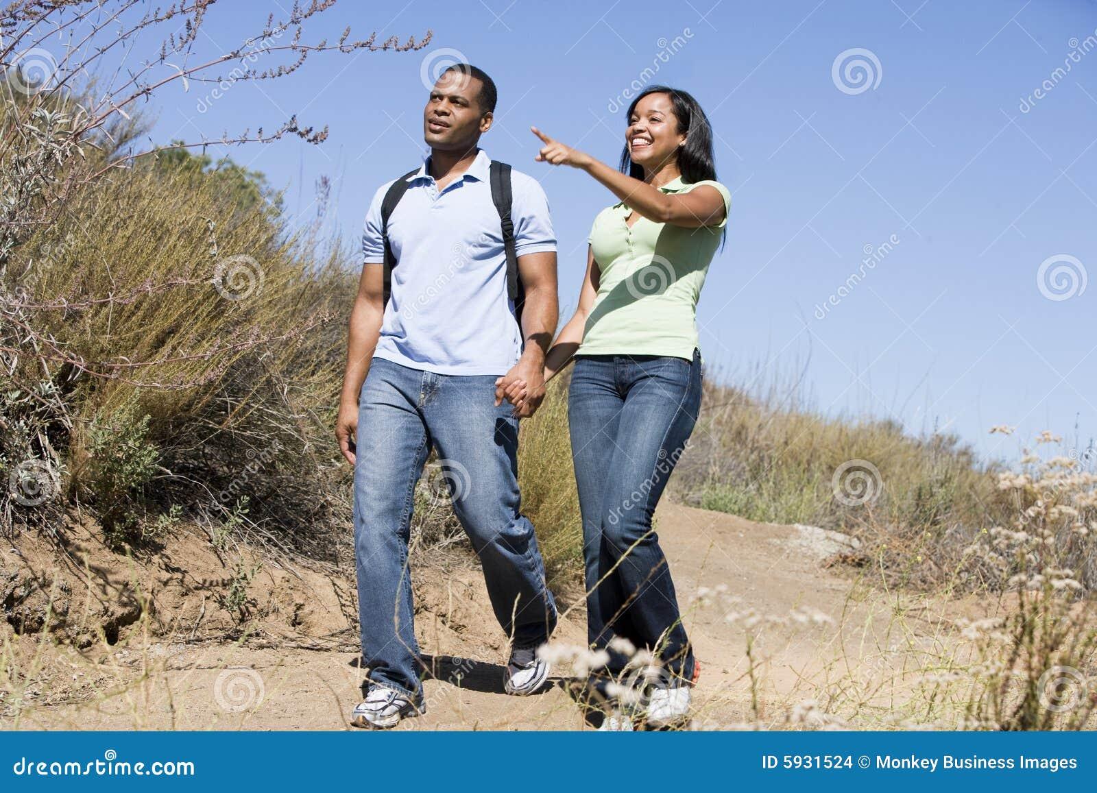 Paar dat bij wegholding handen en het glimlachen loopt