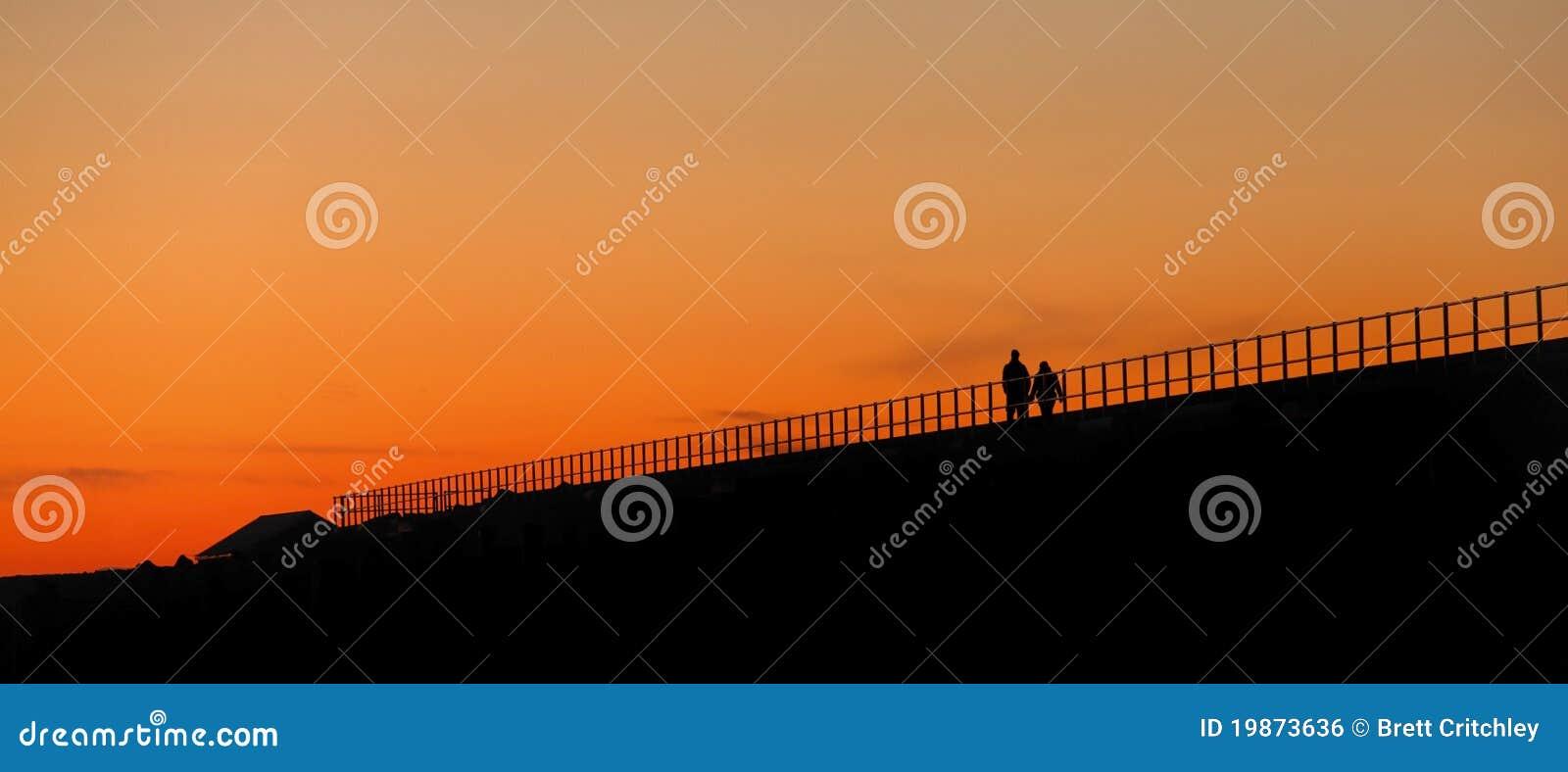 Paar dat bij zonsondergang loopt