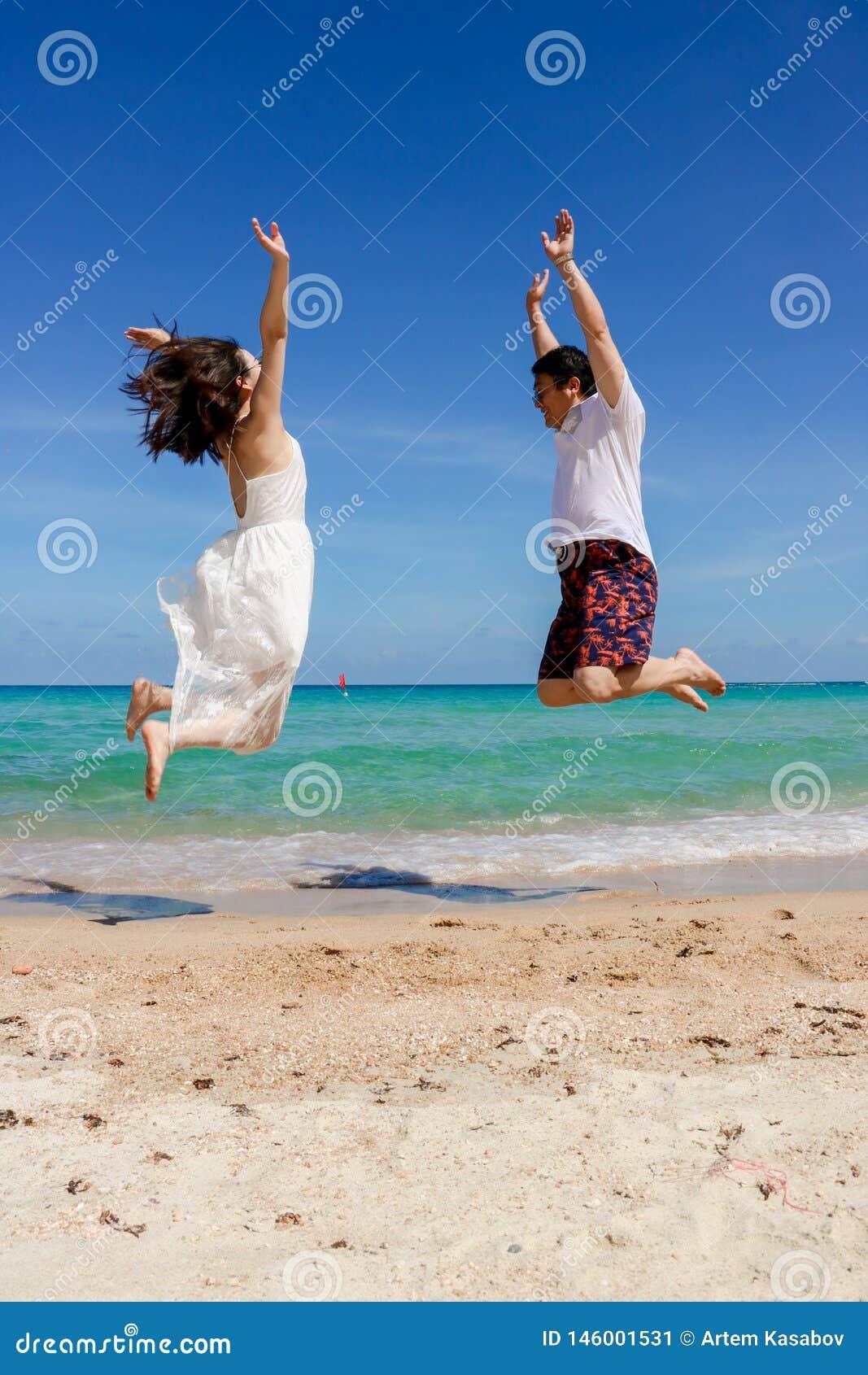 Paar dat op het strand springt