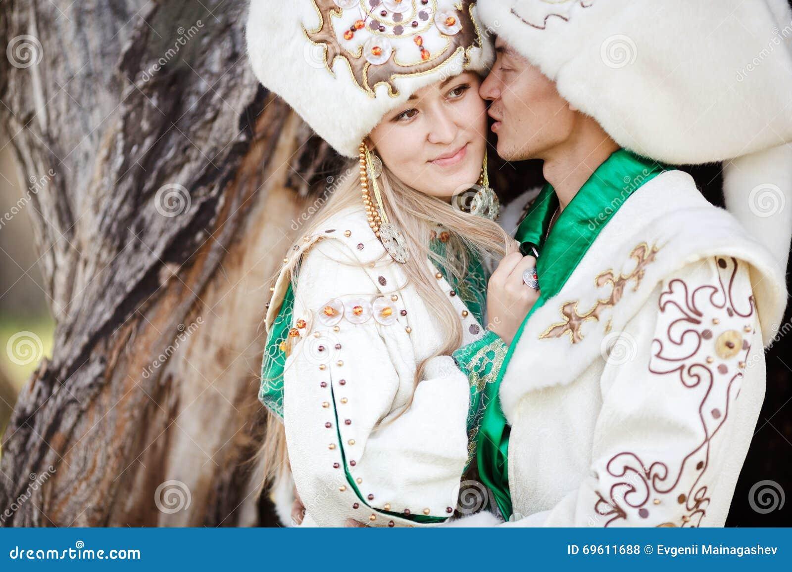 Paar in der Umarmung der ethnischen Kostüme auf Hintergrund des strukturierten Holzes, Bräutigam küsst Braut an der Backe