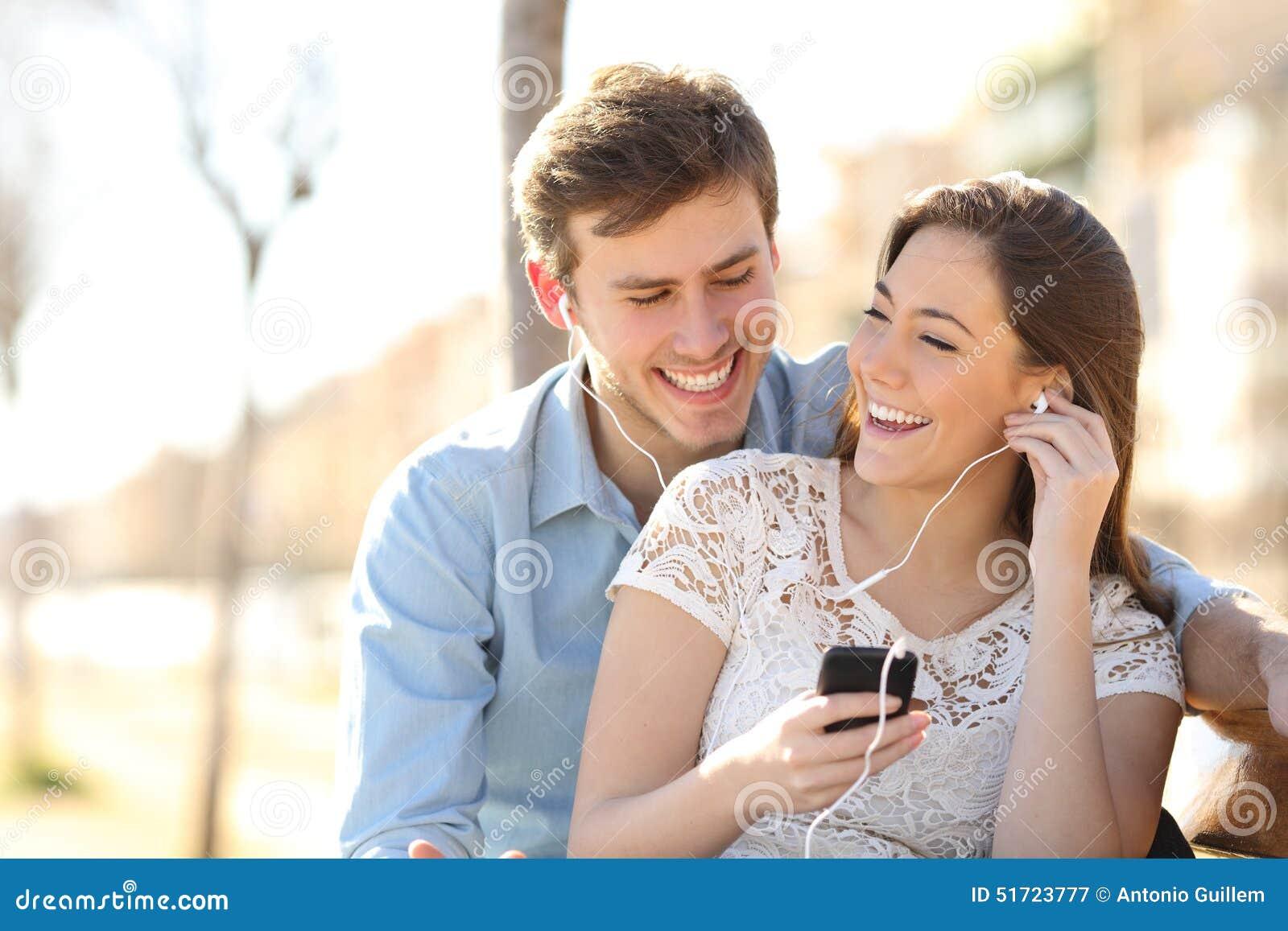 Paar die aan de muziek van een slimme telefoon luisteren