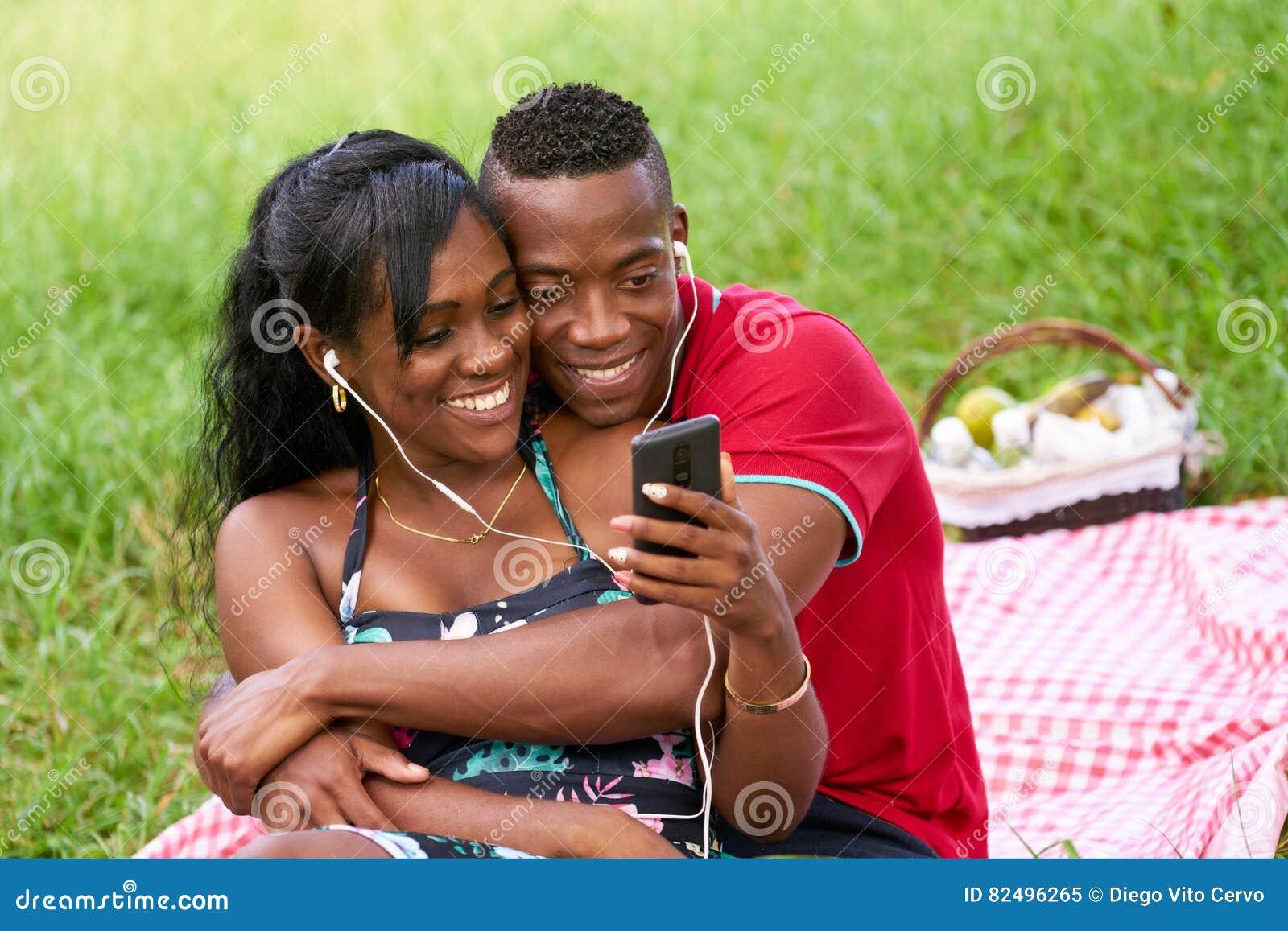 Paar die aan Muziek en het Letten op Video op Mobiele Telefoon luisteren