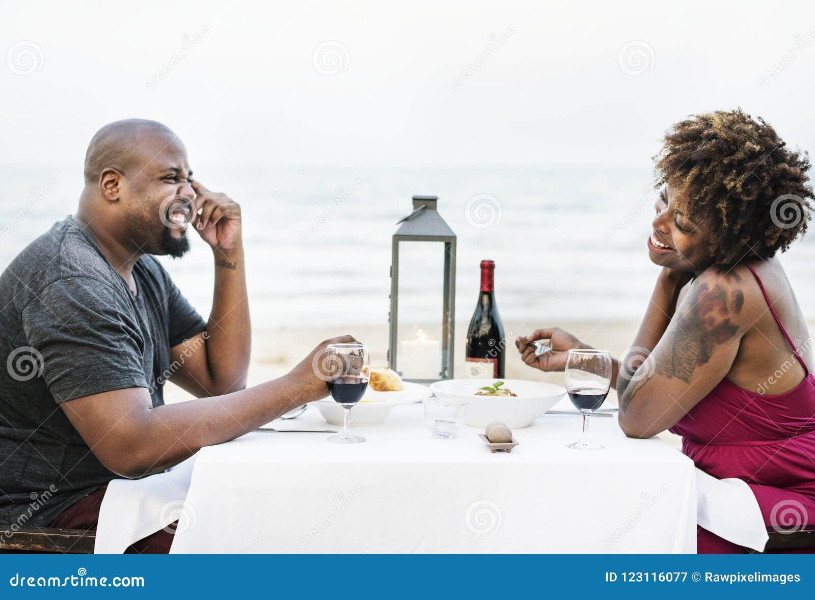 Paar die een romantisch diner hebben bij het strand