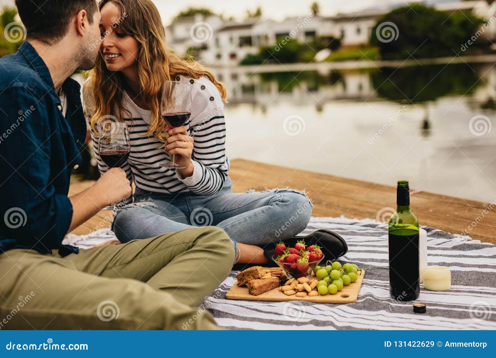 Paar die elkaar op een datumzitting kussen naast een meer Paar in liefdezitting op een houten dok dichtbij een meer het drinken w