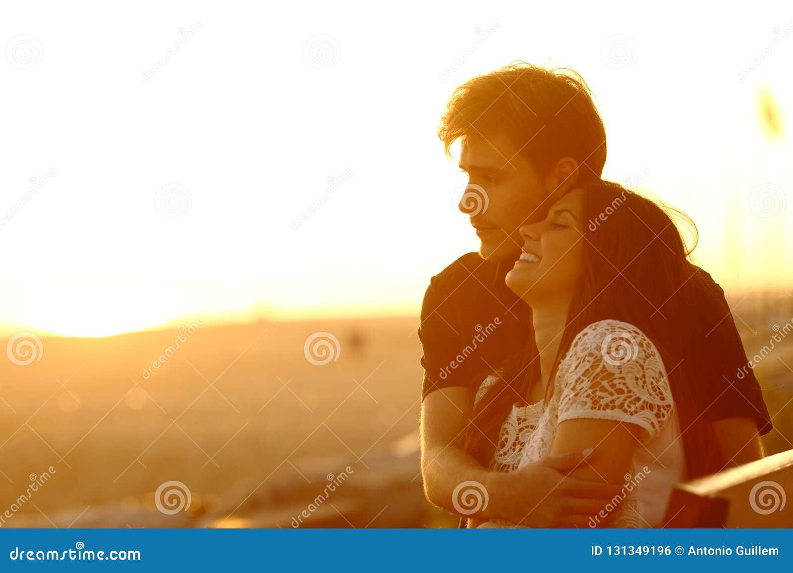Paar die en bij zonsondergang op het strand dateren flirten