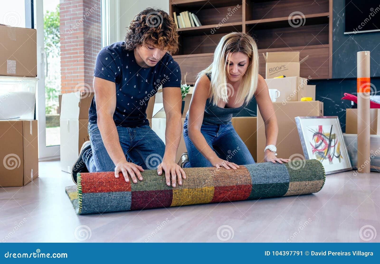 Paar die het tapijt uitrollen