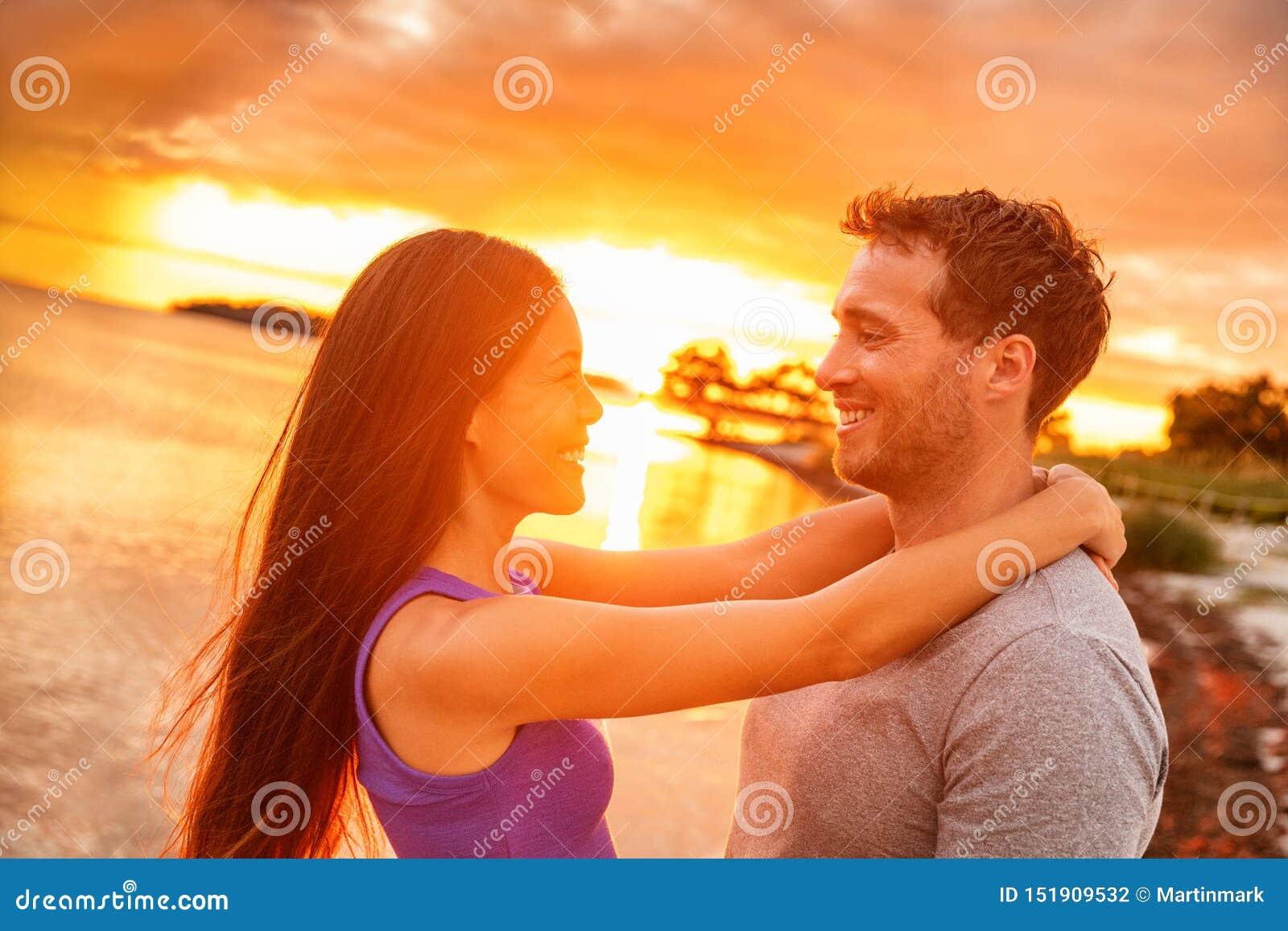 Paar die in liefde bij zonsonderganggloed lachen op de tropische Caraïbische vakantie van het de zomerstrand Gelukkige Aziatische