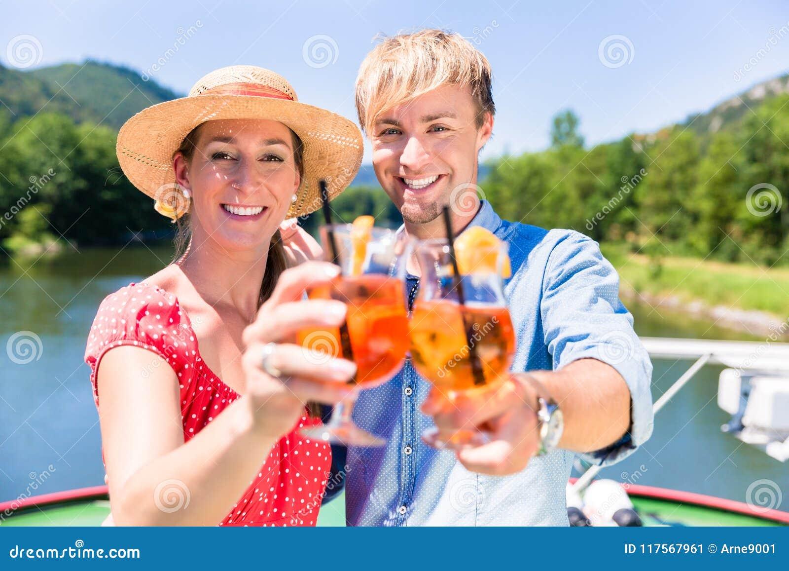 Paar die in liefde op riviercruise coctails in de zomer drinken