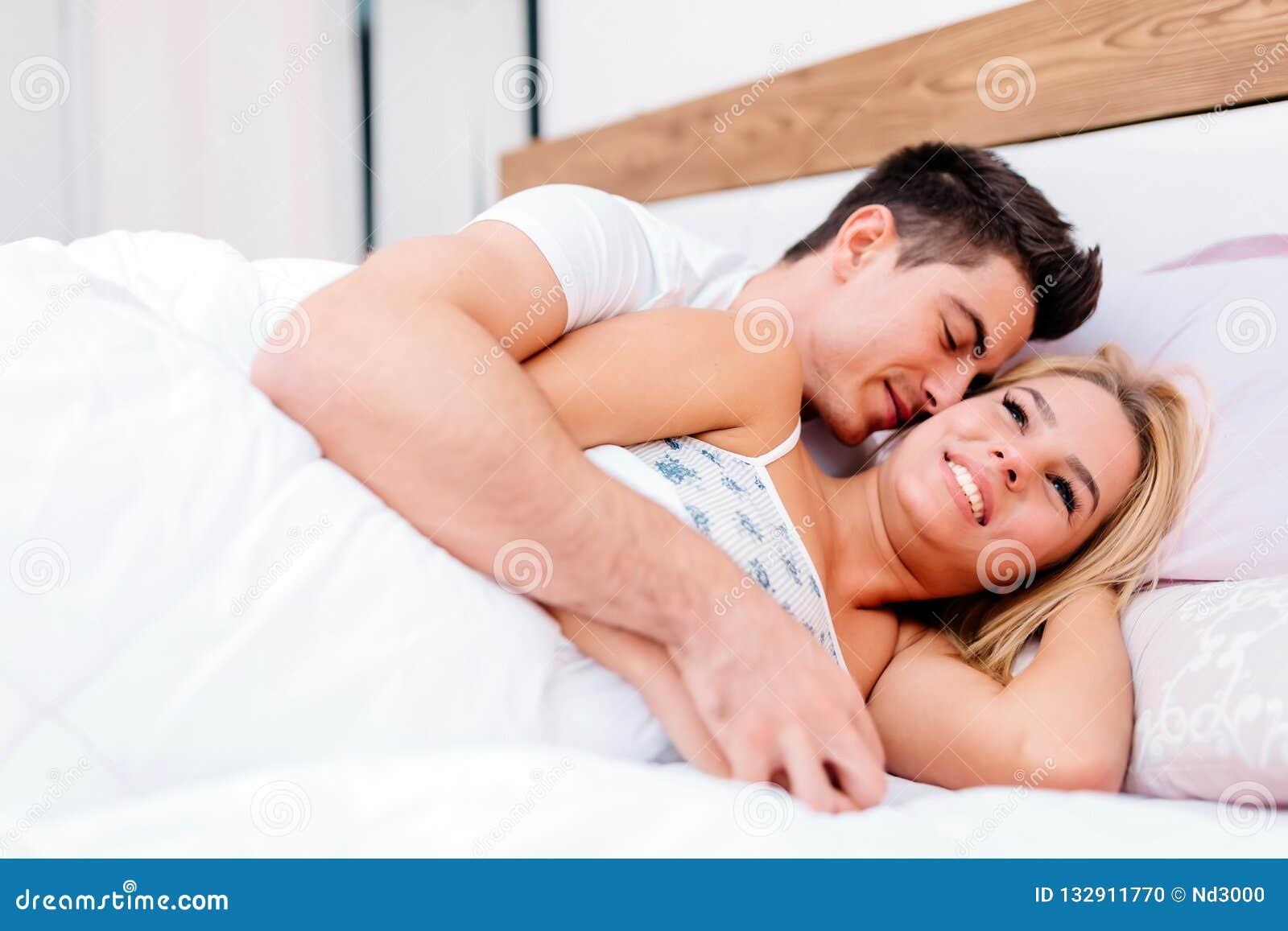 Paar die pret in bed en het glimlachen hebben