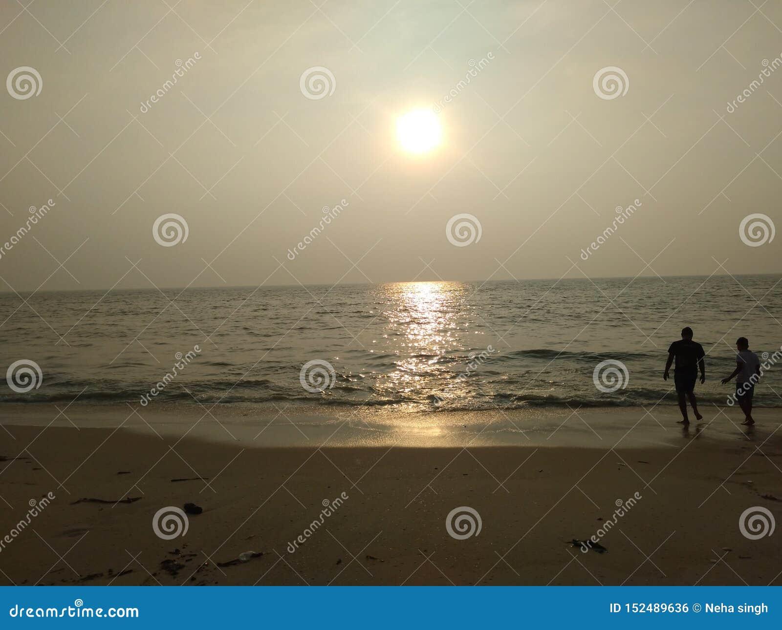 Paar die van het aardige de mening van zonsondergangcalmsea ontspannen genieten