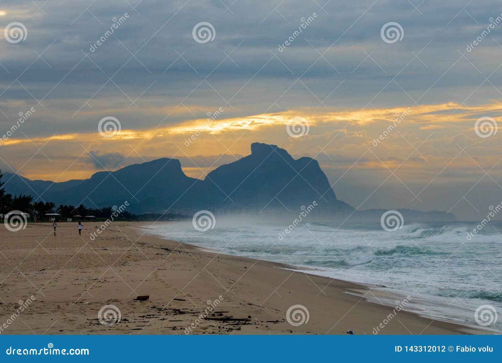 Paar en hond die op het strand van Barra da Tijuca in een mooie dageraad met de steen van Gavea op de achtergrond lopen - Rio de
