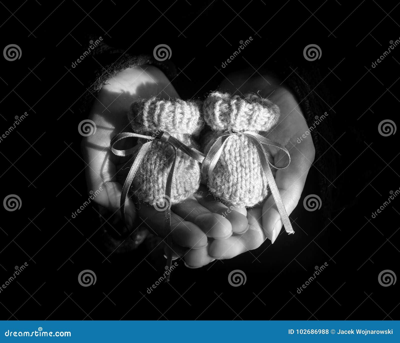 Paar Gebreide Babybuiten in de Hart Gevormde Palmen van een Woma