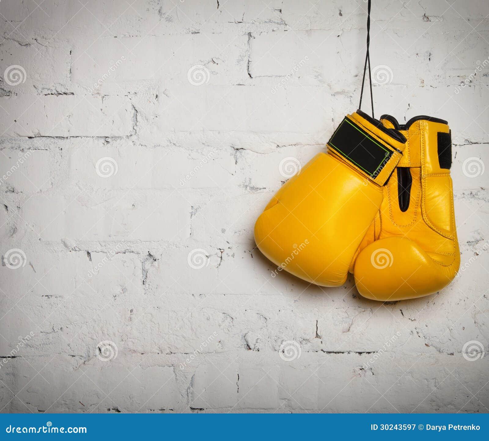 Paar bokshandschoenen die op een muur hangen