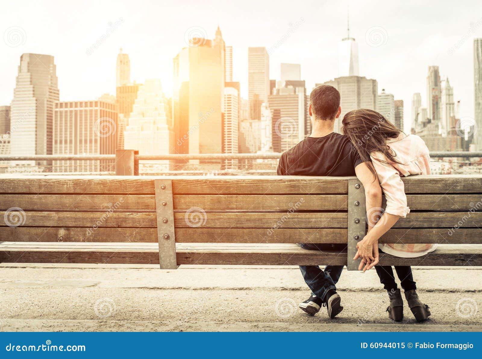 Paar het ontspannen op de bank van New York voor de horizon bij zon