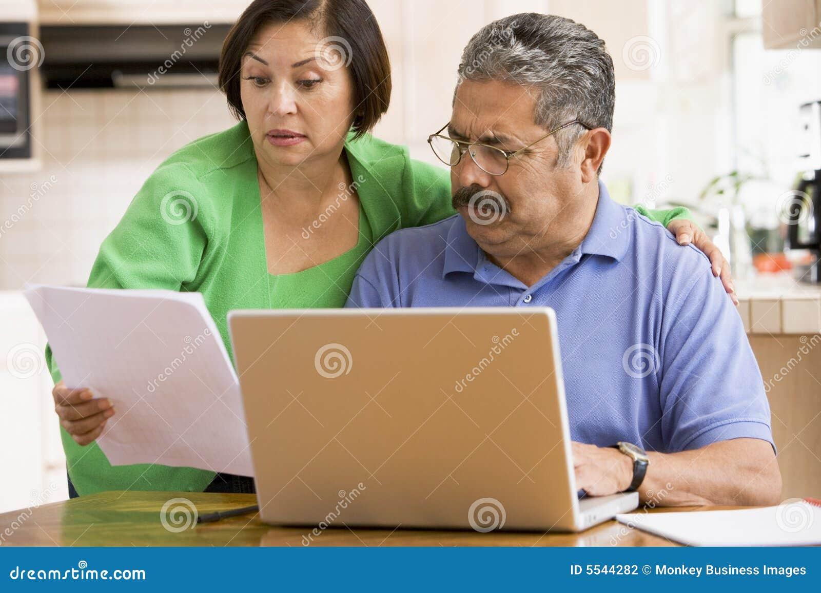 Paar in keuken met laptop en administratie