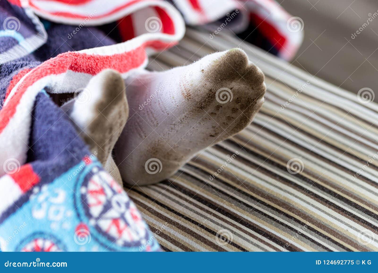 Paar kindvoeten in vuile bevlekte witte sokken Het jonge geitje bevuilde sokken terwijl in openlucht het spelen Kinderenkleren he