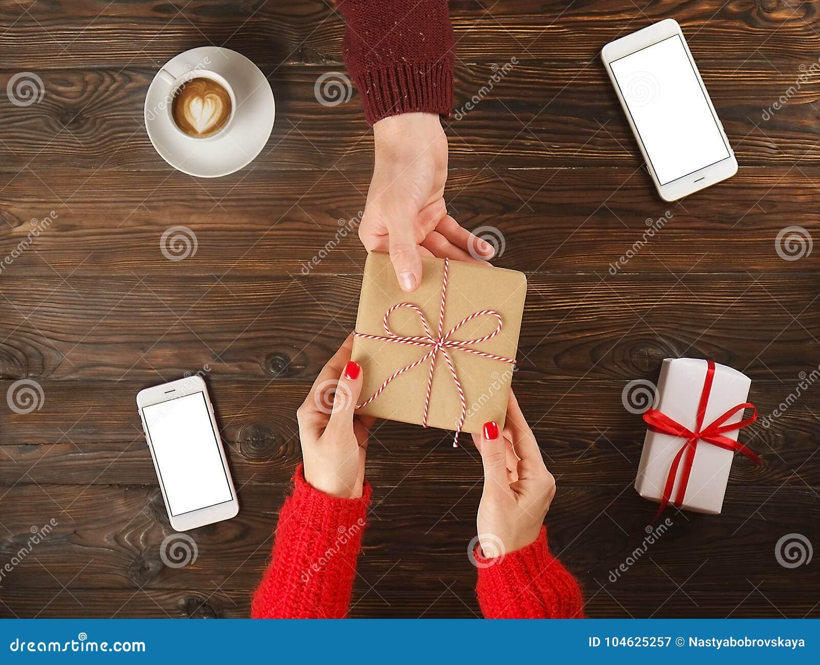 Download Paar In Liefde De Vrouw Geeft Aanwezige De Mens Mens En Vrouwelijke Handen Hoogste Mening Over Houten Lijst Met Telefoons En Koff Stock Afbeelding - Afbeelding bestaande uit gelukkig, gift: 104625257