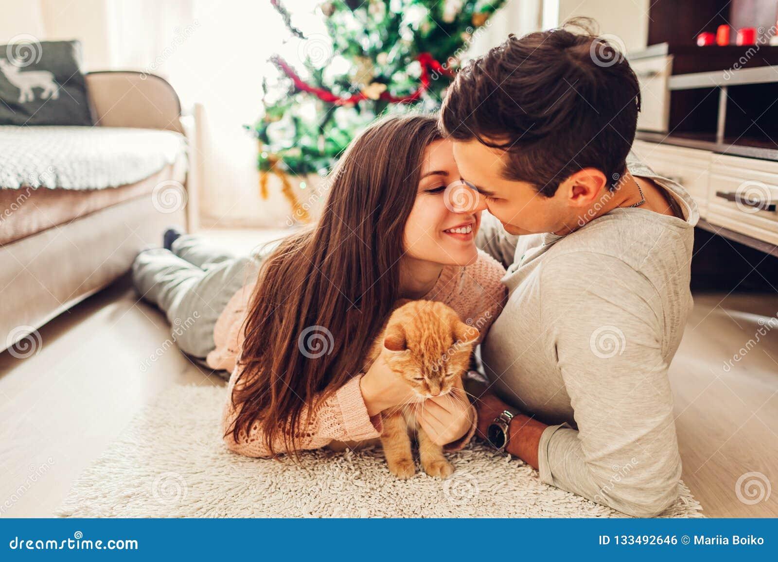 Paar in liefde die door Kerstboom liggen en met kat thuis spelen Het kussen van de man en van de vrouw