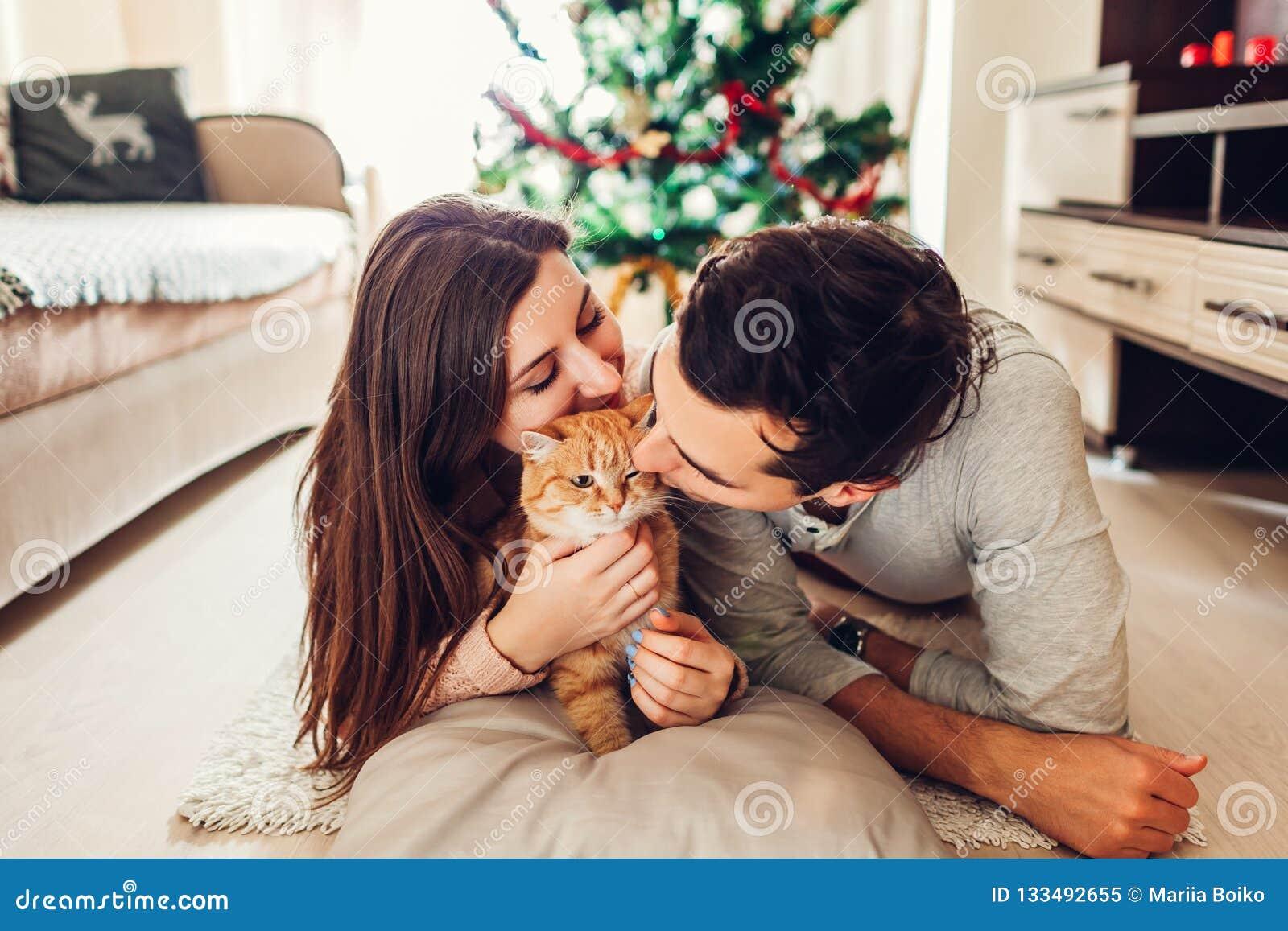 Paar in liefde die door Kerstboom liggen en met kat thuis spelen Het ontspannen van de man en van de vrouw