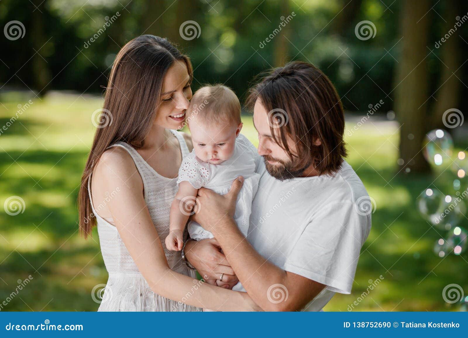 Paar in liefde het gekleed in de witte vrijetijdskleding brengt tijd in het park in een zonnige dag met daar mooie baby door