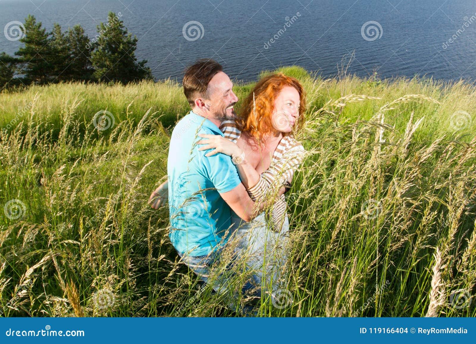 Paar in liefde passionately omhelzing Langverwachte vergadering van de twee minnaars buiten dichtbij van meer Rode haarvrouw en m