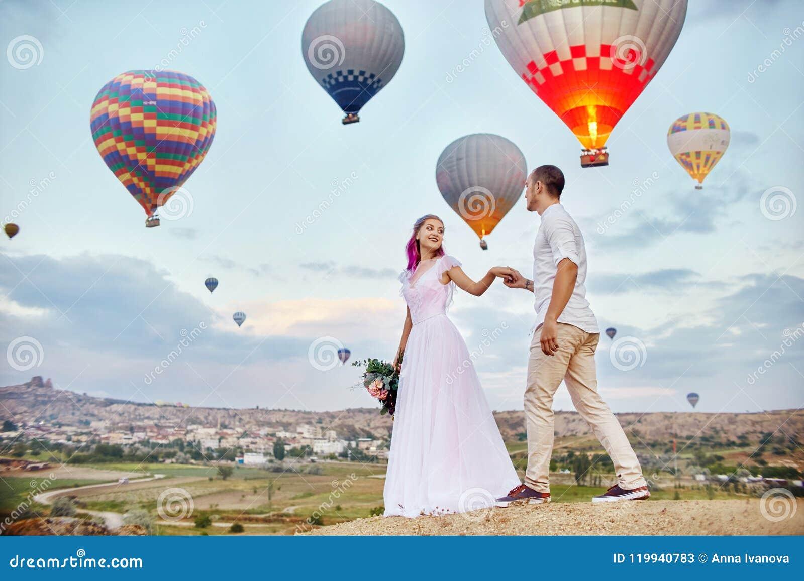 Paar in liefdetribunes op achtergrond van ballons in Cappadocia De man en een vrouw op heuvel bekijken een groot aantal vliegende