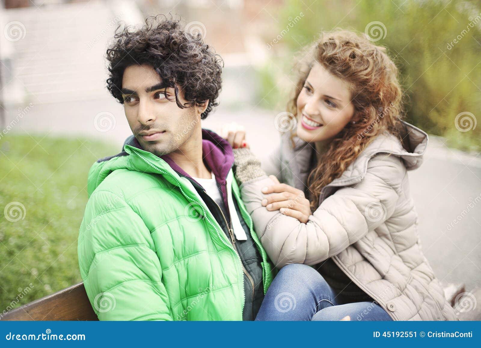 Paar in liefdezitting op een bank in stad