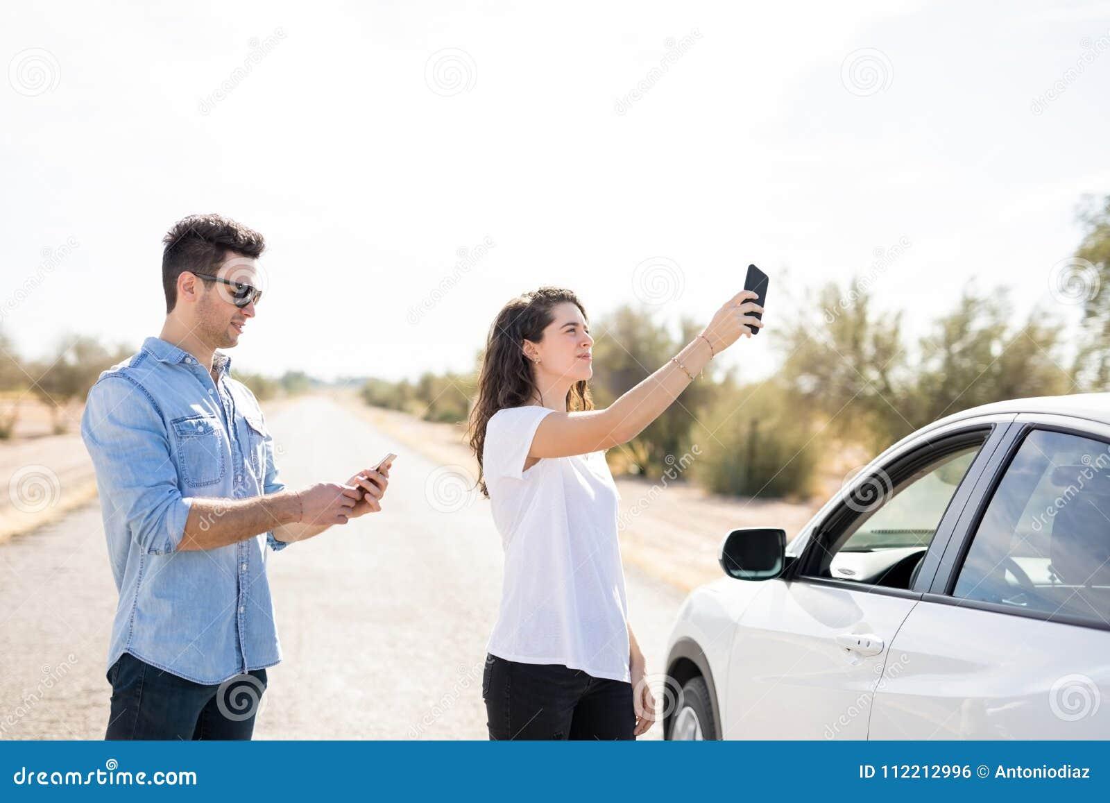 Paar met gebroken auto die naar telefoondekking zoeken
