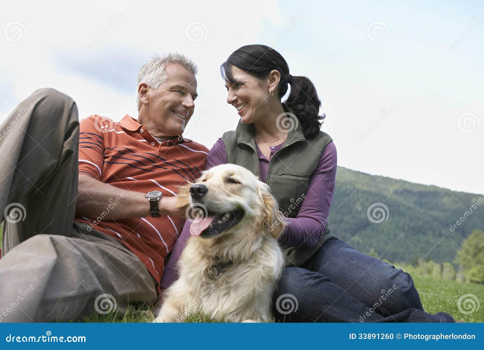 Paar met Golden retriever op Gras