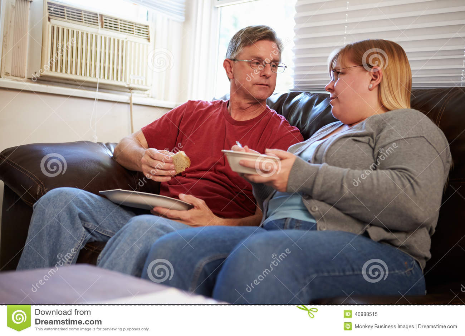 Paar met Slechte Dieetzitting op Sofa Eating Meal
