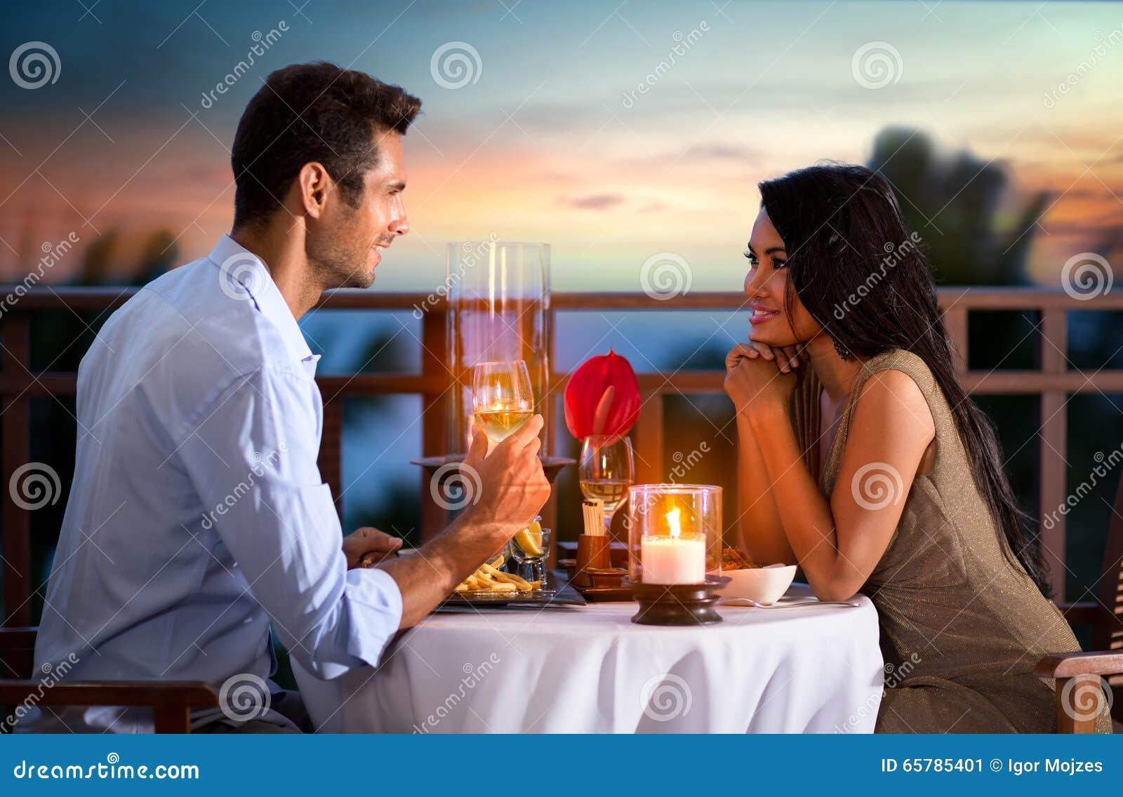 Paar op de zomeravond die romantisch diner hebben